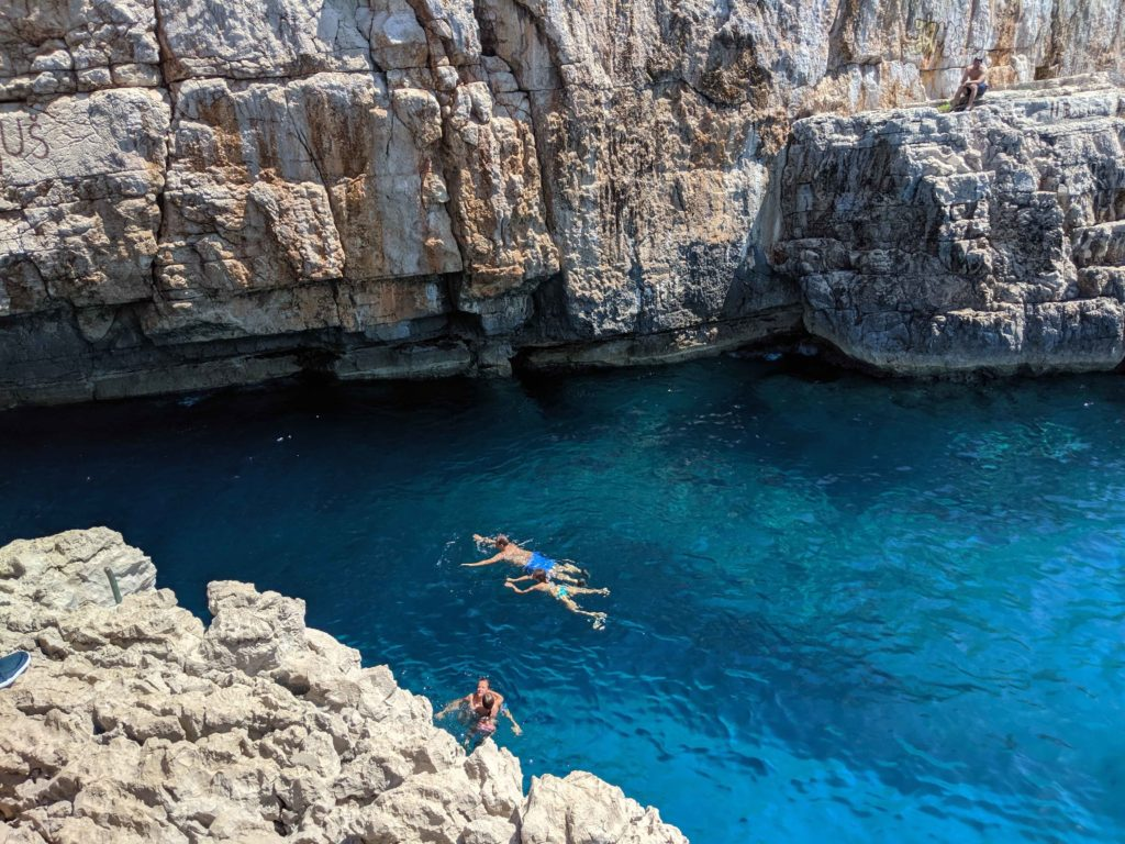 Swimmers enjoy the cool water after taking  the plunge from a nearby cliff - Odyssius Cave, Otok Mljet